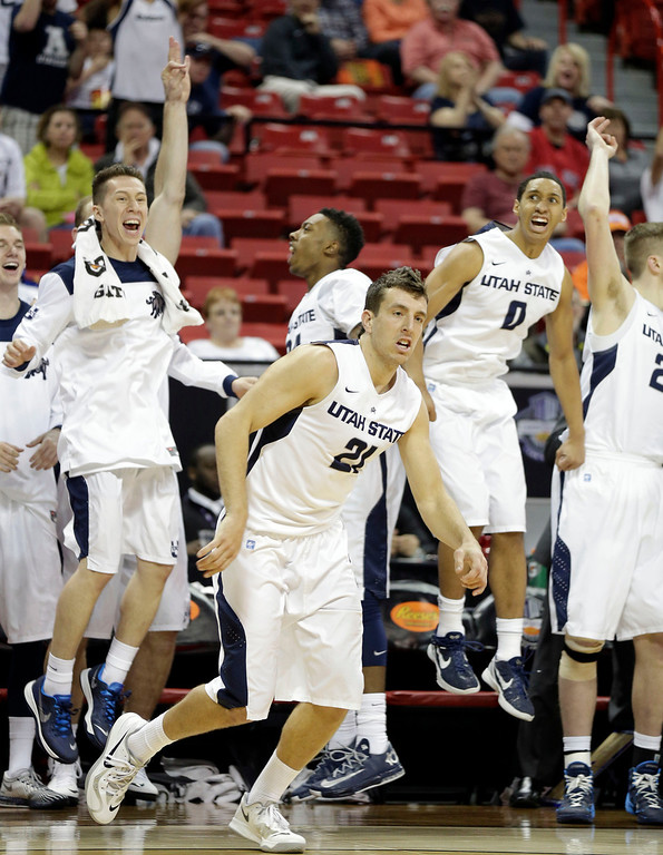 . Utah State\'s bench reacts after Spencer Butterfield (21) sinks a 3-point shot to come within one point of Colorado State during the second half of a Mountain West Conference tournament NCAA college basketball game Wednesday, March 12, 2014, in Las Vegas. Utah State defeated Colorado State 73-69. (AP Photo/Isaac Brekken)