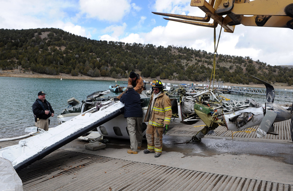 . Ouray County released this photo that shows investigators examine the aircraft after it was recovered with the five victims on Thursday March 27, 2014, at the Ridgway Reservoir near Ridgway, Colo.,  The plane crashed last Saturday, March 22, 2014, killing five people from Alabama. (AP Photo/Ouray County, William Woody)