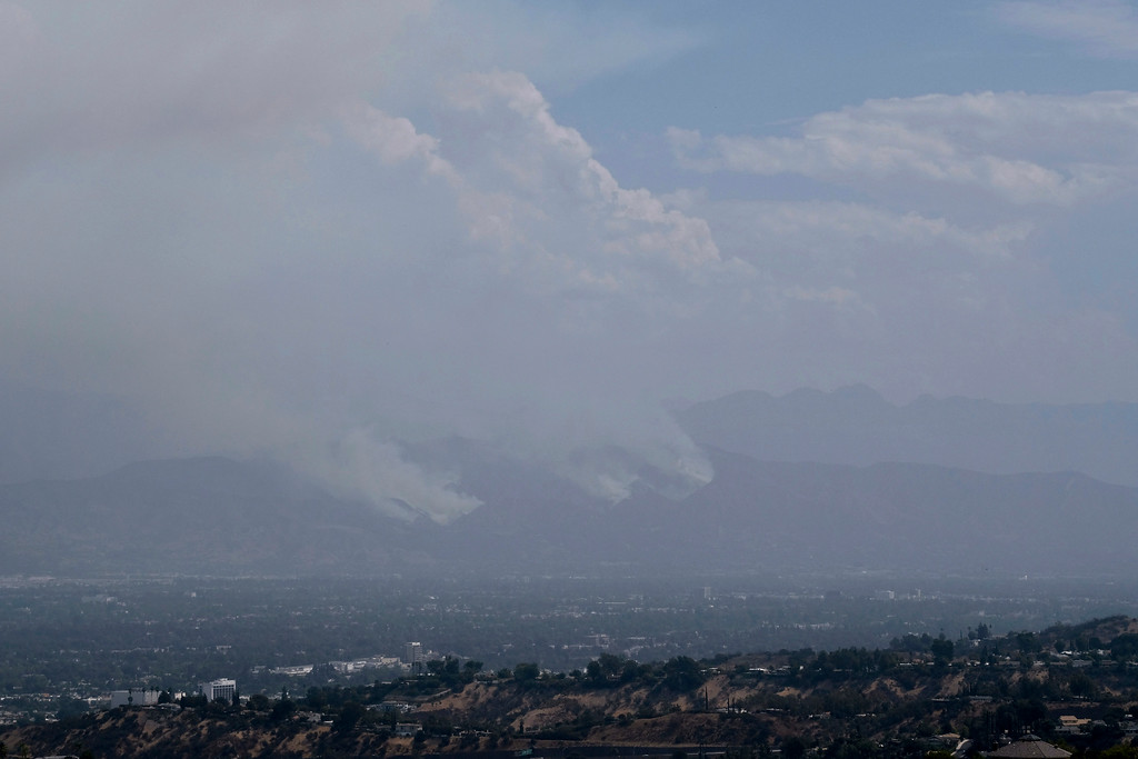 . Dry brush is seen in the Santa Monica mountains, foreground, as the la Tuna Fire burns in the hills of Los Angeles Sunday, Sept. 3, 2017. Smoke filled the sky and ash rained down across Los Angeles Sunday from a destructive wildfire that the mayor said was the largest in city history, one of several blazes that sent thousands fleeing homes across the U.S. West during a blistering holiday weekend heat wave. (AP Photo/Richard Vogel)