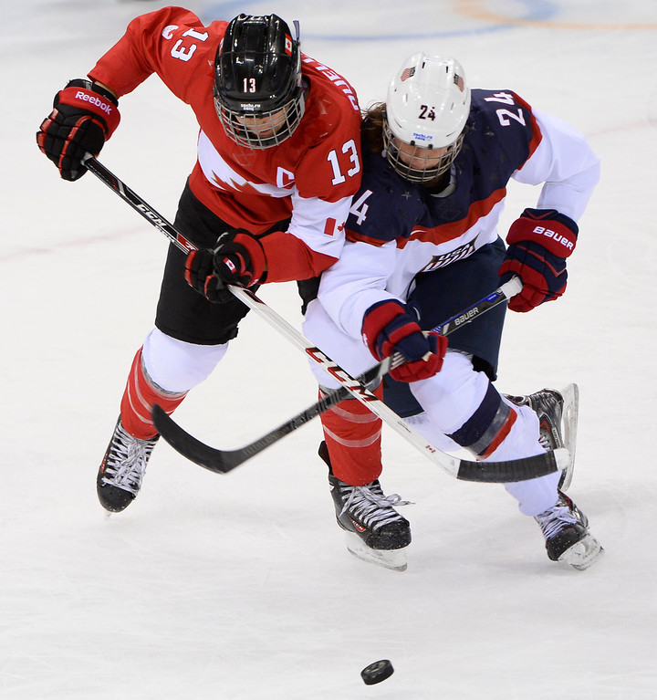 . Canada\'s Caroline Ouellette (L) vies for the puck with US Josephine Pucci during the Women\'s Ice Hockey Group A match between Canada and USA at the Sochi Winter Olympics on February 12, 2014 at the Shayba Arena. AFP PHOTO / JONATHAN NACKSTRAND/AFP/Getty Images