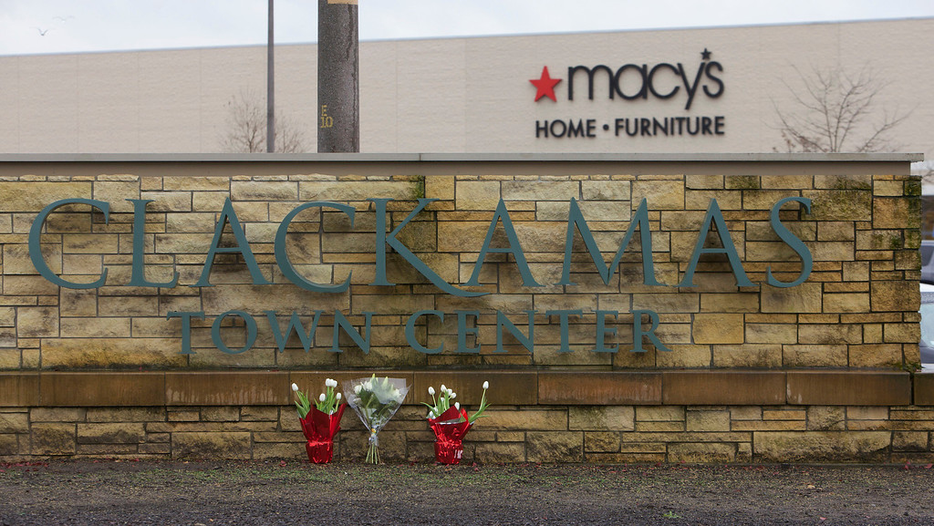 . Flowers are left by a Clackamas Town Center shopping mall sign in Portland, Oregon, December 12, 2012. The masked gunman who opened fire in a crowded Oregon shopping mall, killing two people and wounding a third before taking his own life, appeared to have acted in a blind rampage with no known motive, authorities said on Wednesday. REUTERS/Steve Dipaola