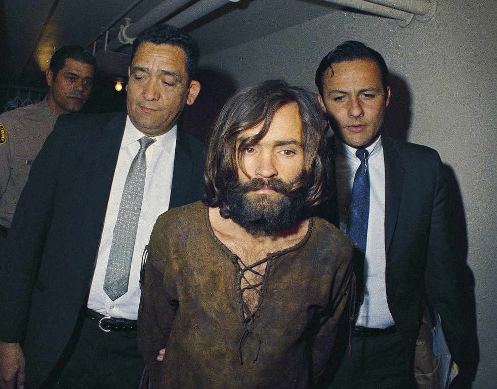 . FILE - In this 1969 file photo, Charles Manson is escorted to his arraignment on conspiracy-murder charges in connection with the Sharon Tate murder case. Authorities say Manson, cult leader and mastermind behind 1969 deaths of actress Sharon Tate and several others, died on Sunday, Nov. 19, 2017. He was 83. (AP Photo, File)