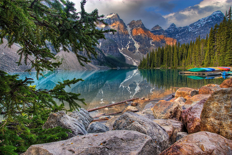 Majestic Canadian Rockies at Moraine Lake at sunrise. Canoes are docked just waiting for the busy tourist onslaught a few hours later. So beautiful and tranquil isn't it.