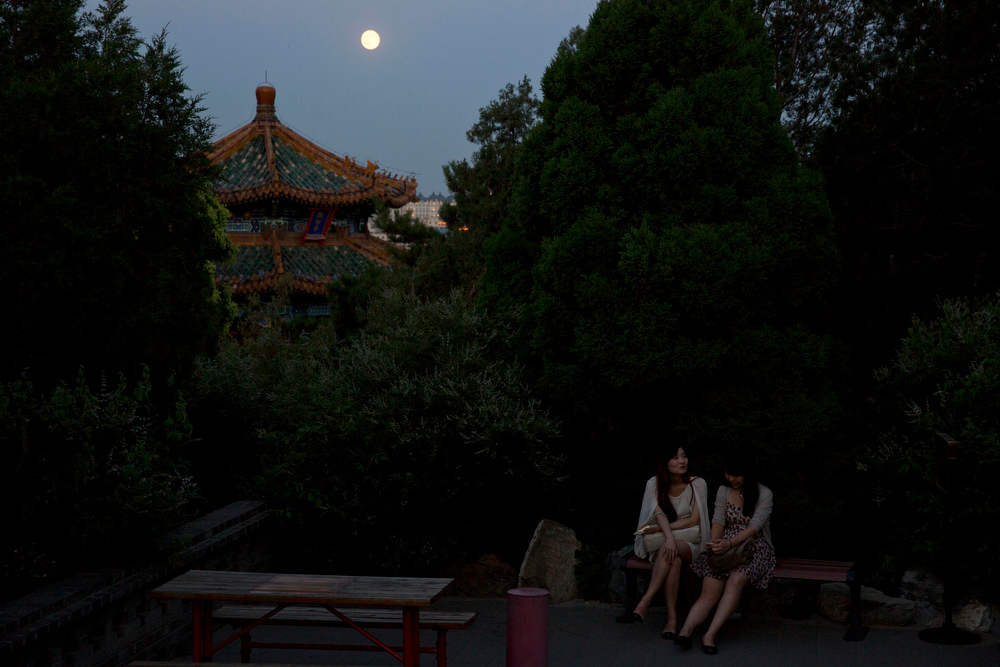 ". Chinese women talk at a park as a perigee moon also known as a supermoon rises behind them in Beijing, China, Saturday, July 12, 2014.  The phenomenon, which scientists call a ""perigee moon,\"" occurs when the moon is near the horizon and appears larger and brighter than other full moons. (AP Photo/Ng Han Guan)"