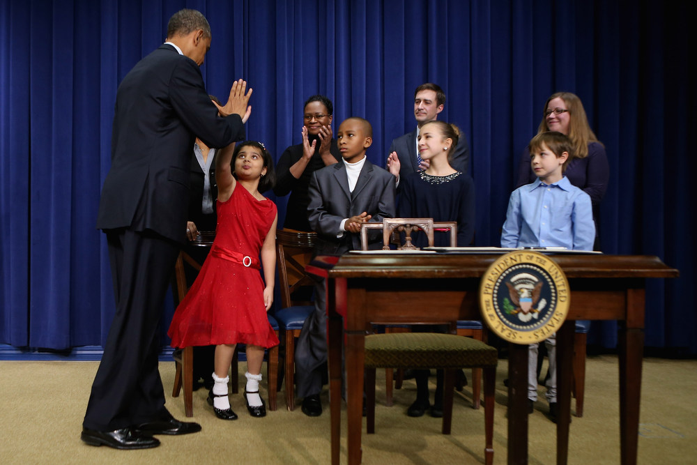 Description of . U.S. President Barack Obama (L) gives high-fives to children who wrote letters to the White House about gun violence, (L-R) Hinna Zeejah, Taejah Goode, Julia Stokes and Grant Fritz, after announcing the administration's new gun law proposals in the Eisenhower Executive Office building January 16, 2013 in Washington, DC. The president unveiled a package of gun control proposals that include universal background checks and bans on assault weapons and high-capacity magazines.  (Photo by Chip Somodevilla/Getty Images)