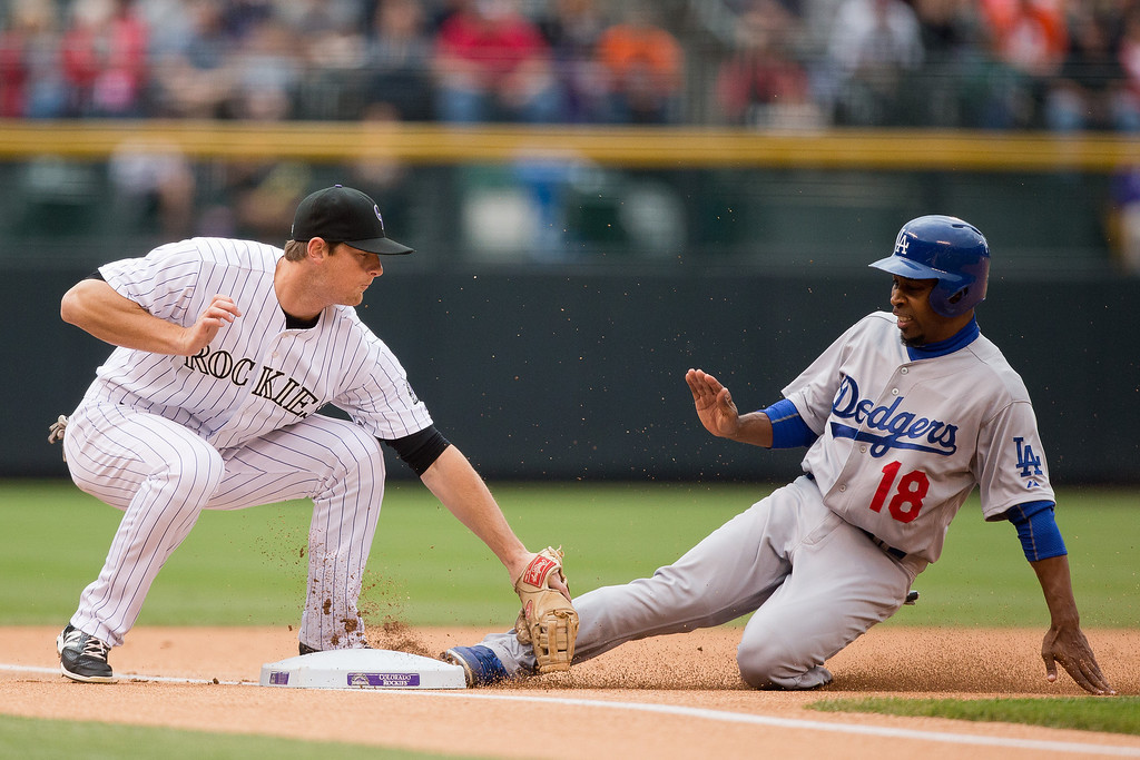 . Chone Figgins #18 of the Los Angeles Dodgers steals third base before the tag by DJ LeMahieu #9 of the Colorado Rockies during the first inning at Coors Field on June 8, 2014 in Denver, Colorado. (Photo by Justin Edmonds/Getty Images)