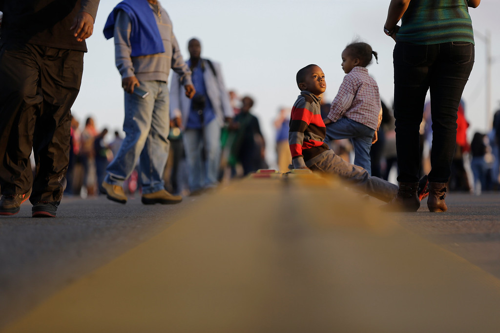 ". Children and others walk and sit on the Edmund Pettus Bridge, Saturday, March 7, 2015, in Selma, Ala. This weekend marks the 50th anniversary of ""Bloody Sunday,\"" a civil rights march in which protesters were beaten, trampled and tear-gassed by police at the Edmund Pettus Bridge in Selma, Ala. (AP Photo/Gerald Herbert)"
