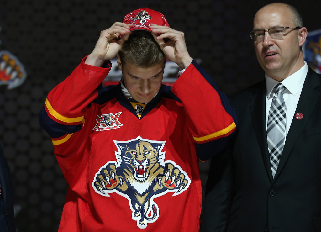 . Aleksander Barkov puts on his hat with Director of Scouting Scott Luce after being selected number two over all in the first round by the Florida Panthers during the 2013 NHL Draft at the Prudential Center on June 30, 2013 in Newark, New Jersey.  (Photo by Bruce Bennett/Getty Images)