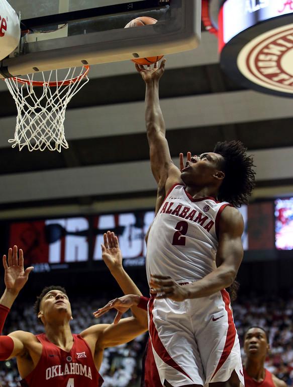 . Alabama guard Collin Sexton (2) puts up a shot over Oklahoma center Jamuni McNeace (4) during the second half of an NCAA college basketball game, Saturday, Jan. 27, 2018, in Tuscaloosa, Ala. Alabama won 80-73. (AP Photo/Butch Dill)