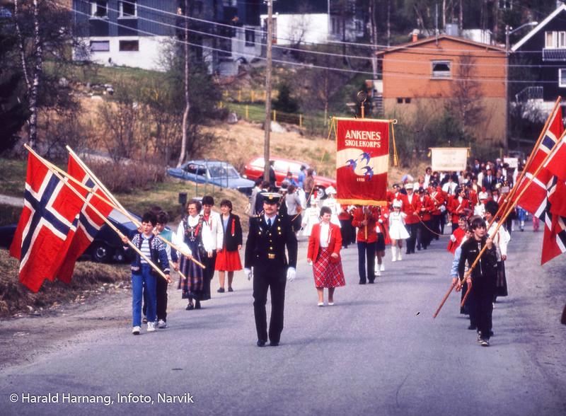 17. mai-barnetoget på Ankenes.  Bilde tatt bortover gamle Ankenesveien. Ankenes skolelkorps spiller. Flaggborg. Baard Mikalsen, politi, går forrest. Bilde fra siste halvdel av 1980-tallet.