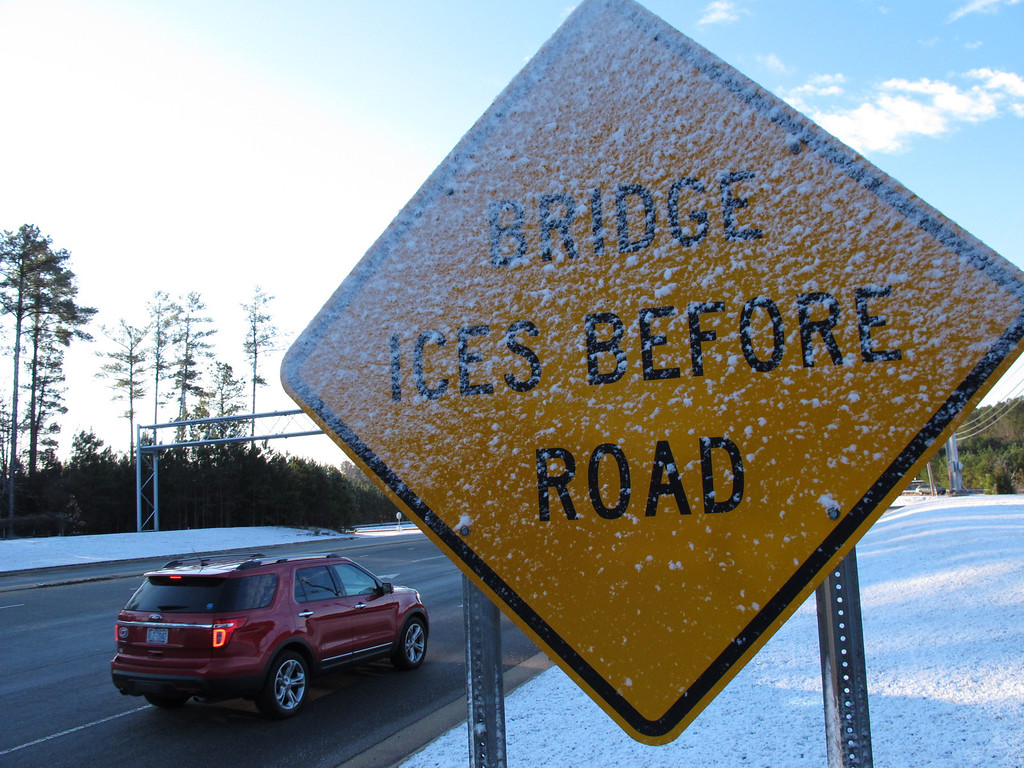 . Icy snow plasters a warning sign near Interstate 540 in Raleigh, N.C., on Wednesday, Jan. 22, 2014. The area got a dusting, prompting officials to delay school openings. (AP Photo/Allen G. Breed)