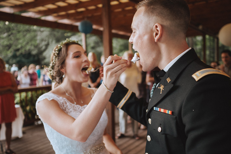 The bride and groom feed each other cake as wedding guests watch.