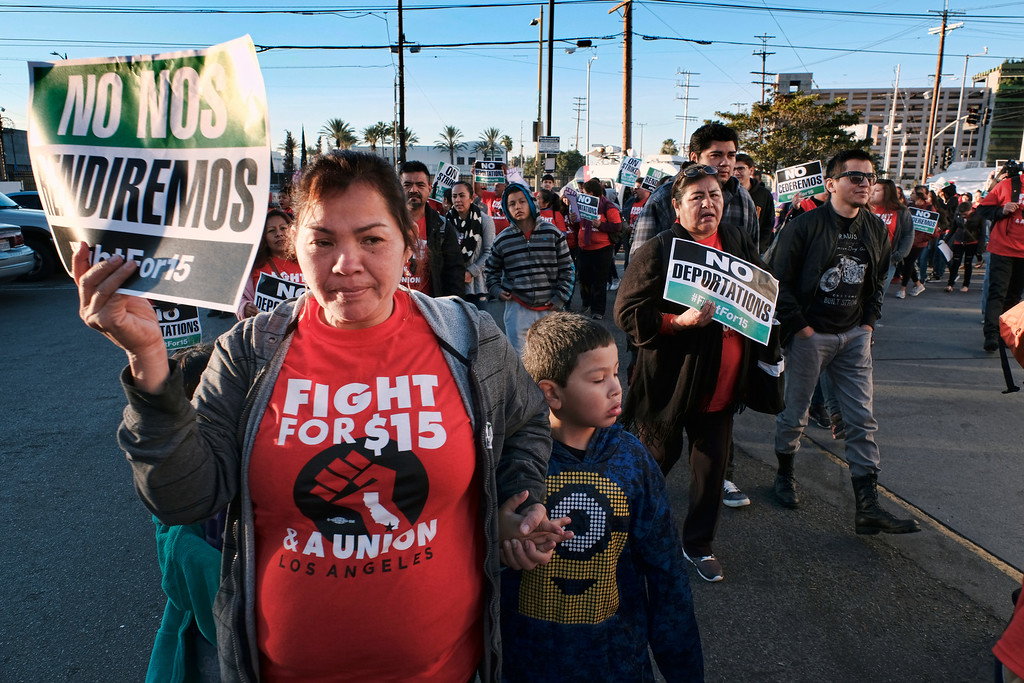 ". Protesters carrying signs and chanting slogans march during a wage protest in downtown Los Angeles on Tuesday, Nov. 29, 2016. A few dozen protesters blocked a downtown Los Angeles intersection as part of a national wave of demonstrations in support of higher wages and workers\' rights. Police stood by as the peaceful demonstrators formed a circle in the street early Tuesday while hoisting signs saying ""the whole world is watching\"" and \""Fight for $15.\"" (AP Photo/Richard Vogel)"