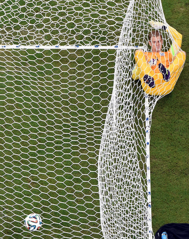 . England\'s goalkeeper Joe Hart lies on the net after Italy\'s forward Mario Balotelli (not pictured) scored during a Group D football match between England and Italy at the Amazonia Arena in Manaus during the 2014 FIFA World Cup on June 14, 2014.      POOL  AFP PHOTO / FRANCOIS XAVIER MARIT