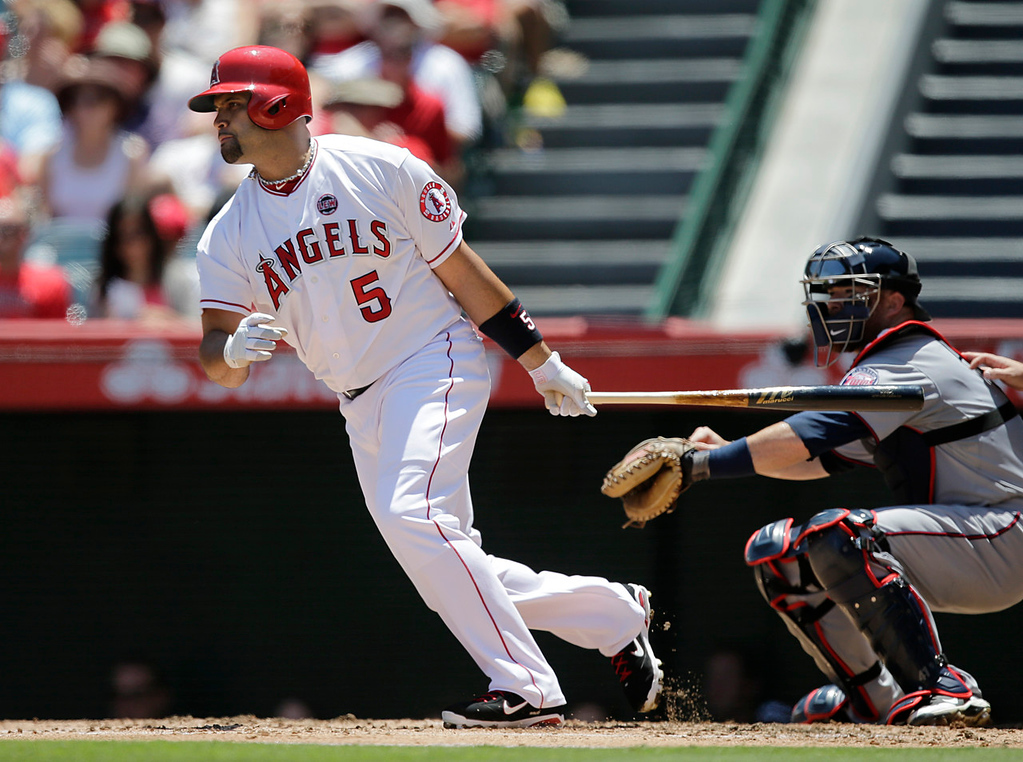 . Angels batter Albert Pujols hits an RBI-single to center during the first inning against the Twins. Minnesota catcher Chris Herrmann is at right.  (AP Photo/Jae C. Hong)