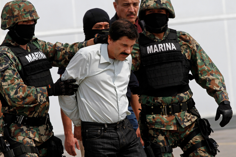 """. Joaquin \""""El Chapo\"""" Guzman is escorted to a helicopter in handcuffs by Mexican navy marines at a navy hanger in Mexico City, Saturday, Feb. 22, 2014. A senior U.S. law enforcement official said Saturday, that Guzman, the head of Mexico�s Sinaloa Cartel, was captured alive overnight in the beach resort town of Mazatlan. Guzman faces multiple federal drug trafficking indictments in the U.S. and is on the Drug Enforcement Administration�s most-wanted list. (AP Photo/Marco Ugarte)"""