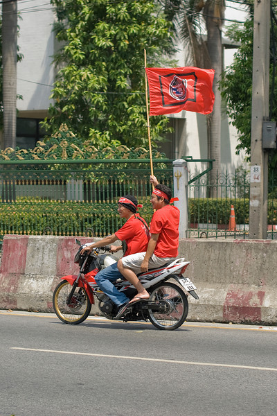 Man waving flag while riding on a motorcycle during Red Shirt Protest in Thailand