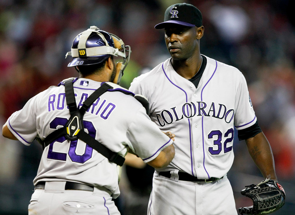 . Colorado Rockies catcher Wilin Rosario (20) and relief pitcher LaTroy Hawkins (32) celebrate after defeating the Arizona Diamondbacks 5-3 in 10 innings in a baseball game, Sunday, Aug. 10, 2014, in Phoenix. (AP Photo/Rick Scuteri)