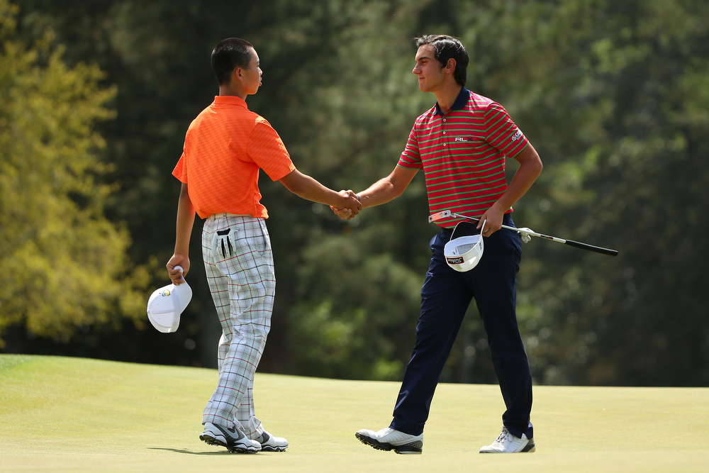 Description of . Tianlang Guan of China shakes with Matteo Manassero of Italy after the second round of the 2013 Masters Tournament at Augusta National Golf Club on April 12, 2013 in Augusta, Georgia.  (Photo by Mike Ehrmann/Getty Images)