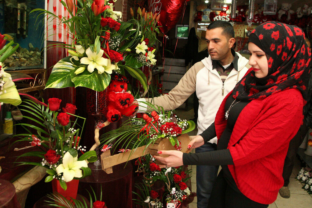 . A vendor helps a woman to select her gift on Valentine\'s Day in Amman February 14, 2013. REUTERS/Majed Jaber