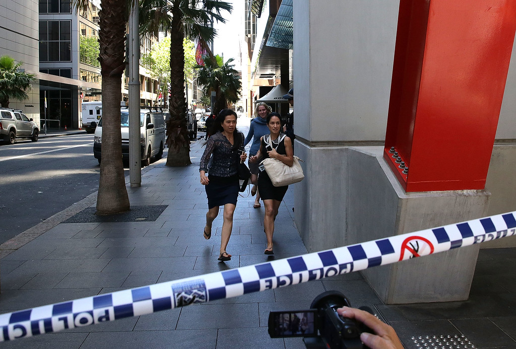 . SYDNEY, AUSTRALIA - DECEMBER 15:  Ladies rush through Philip St past armed police at Lindt Cafe, Martin Place on December 15, 2014 in Sydney, Australia.  Police attend a hostage situation at Lindt Cafe in Martin Place.  (Photo by Mark Metcalfe/Getty Images)