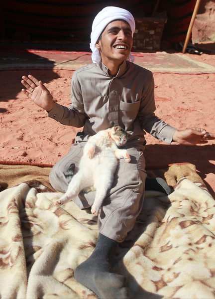 This man was enjoying the way the cat was basking in the sun.