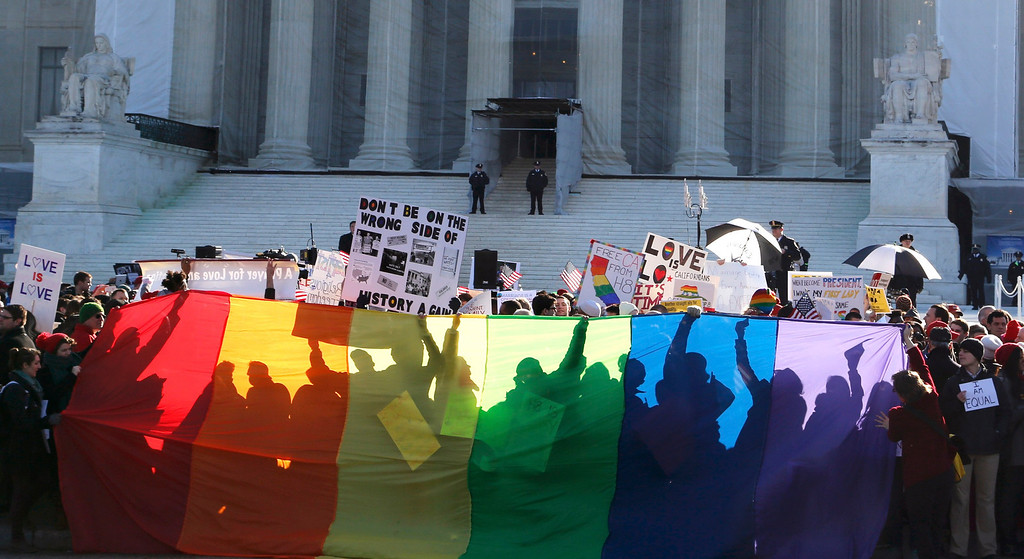 . Anti-Proposition 8 protesters are shadowed by a rainbow banner in front of the U.S. Supreme Court in Washington, March 26, 2013.. REUTERS/Jonathan Ernst