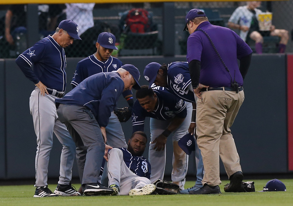 . San Diego Padres left fielder Abraham Almonte, front center, is helped by a trainer and teammates after he fell while trying to field a hit off the bat of Colorado Rockies\' Josh Rutledge in the third inning of a baseball game in Denver on Saturday, Sept. 6, 2014. Almonte remained in the game. (AP Photo/David Zalubowski)