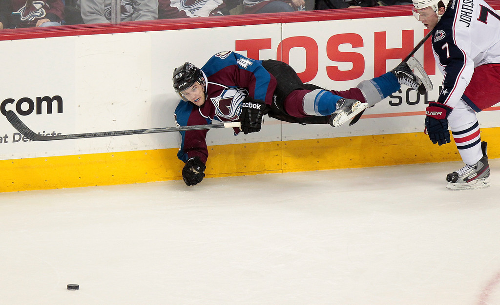 . Colorado Avalanche\'s Stefan Elliott (46) flies through the air after being pushed by Columbus Blue Jackets\' Jack Johnson (7) during the third period of an NHL hockey game on Monday, April 15, 2013 in Denver. The Blue Jackets won 4-3 in Overtime. (AP Photo/Barry Gutierrez)