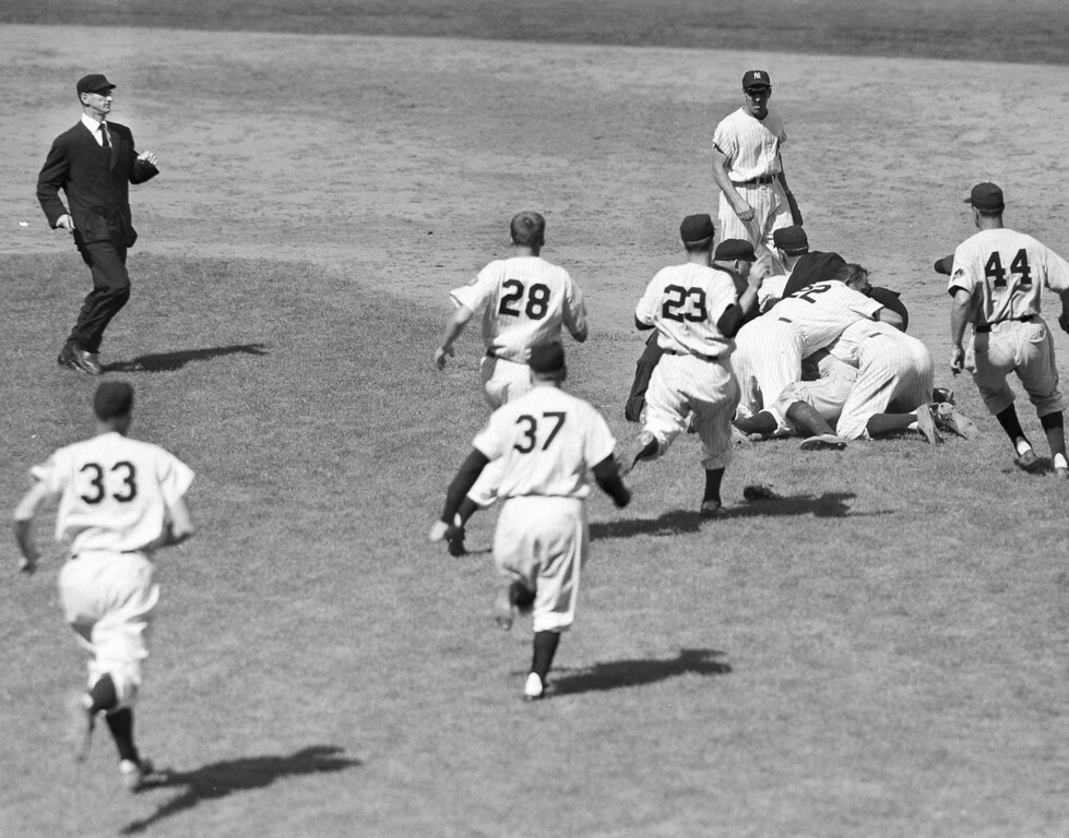 . Players and umpires struggle to pull apart St. Louis Cardinals\' catcher Clint Courtney and New York Yankees\' second baseman Billy Martin after they came to blows at the end of the first half of the eighth inning at Yankee Stadium in New York, July 12, 1952.  On top of the pile is Yankee pitcher Allie Reynolds (22), while Bill Miller (23) rushes in at left.  Shortstop Phil Rizzuto looks on in the background and the umpire at left is Bill Summers.  (AP Photo/Jacob Harris)