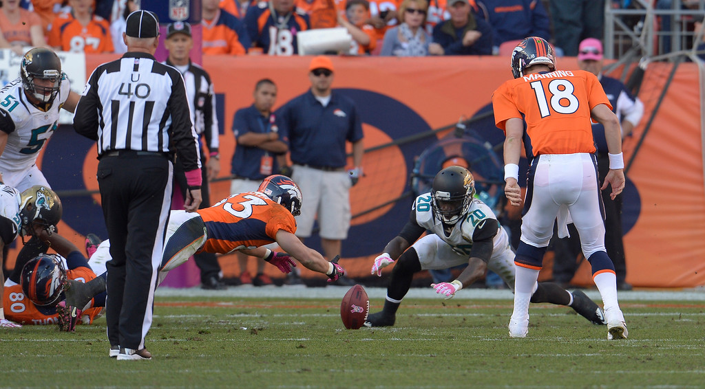 . Denver Broncos quarterback Peyton Manning (18) fumbles the snap as Denver Broncos wide receiver Wes Welker (83) and Jacksonville Jaguars cornerback Mike Harris (20) try to recover it in the fourth quarter. The Jaguars recovered the fumble. (Photo by Joe Amon/The Denver Post)
