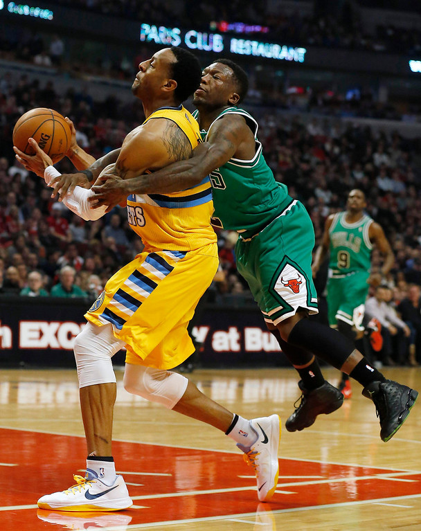 . Chicago Bulls\' Nate Robinson (R) grabs Denver Nuggets\' Andre Iguodala as he fouls him during the first half of their NBA basketball game in Chicago, Illinois, March 18, 2013. REUTERS/Jim Young