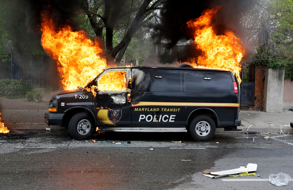 . A police vehicle burns, Monday, April 27, 2015, during unrest following the funeral of Freddie Gray in Baltimore. Gray died from spinal injuries about a week after he was arrested and transported in a Baltimore Police Department van. (AP Photo/Patrick Semansky)