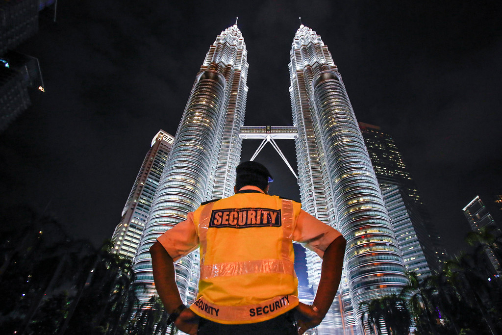 . A security guard stands guard in front of Malaysia\'s iconic building, Petronas Twin Towers in Kuala Lumpur, Malaysia, Thursday, Jan. 14, 2016. Malaysia\'s national police chief Khalid Abu Bakar says police have raised security alert to the highest level following the deadly attack in Jakarta. (AP Photo/Joshua Paul)