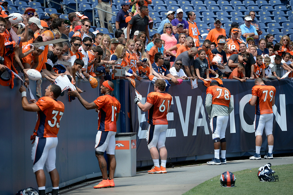 . Denver Broncos sign autographs after practice on day four of the Denver Broncos 2014 training camp July 27, 2014 at Sports Authority Field at Mile High. (Photo by John Leyba/The Denver Post)