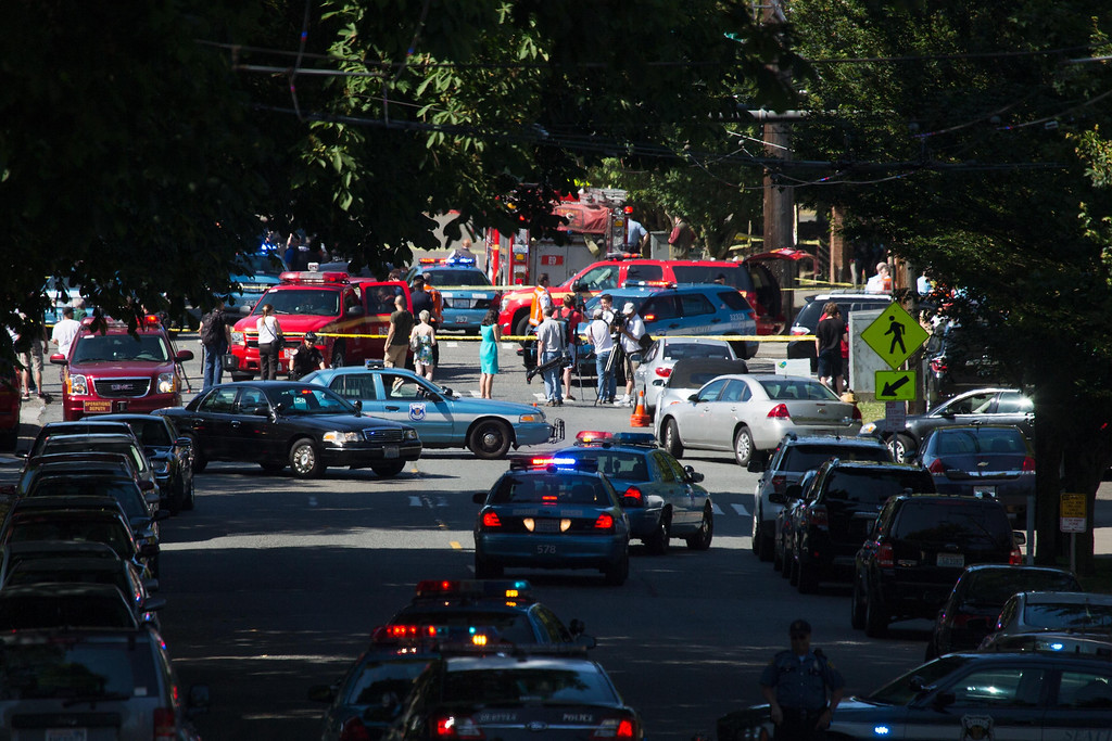 . Media and others gather near the site of a shooting at the Seattle Pacific University campus, in Seattle on Thursday, June 5, 2014. Police say a student at the university disarmed a lone gunman who entered a building and shot four people. A hospital spokeswoman says one man has died and three other people are injured, one critically. (AP Photo/The Seattle Times, Marcus Yam)