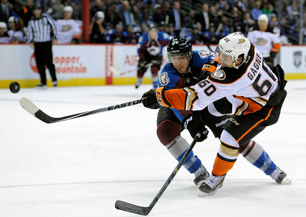 . Anaheim Ducks defenseman Kevin Gagne, right, shoots past Colorado Avalanche defenseman Duncan Siemens, left, in the second period of an NHL preseason hockey game Monday, Sept. 22, 2014, in Denver. (AP Photo/Chris Schneider)