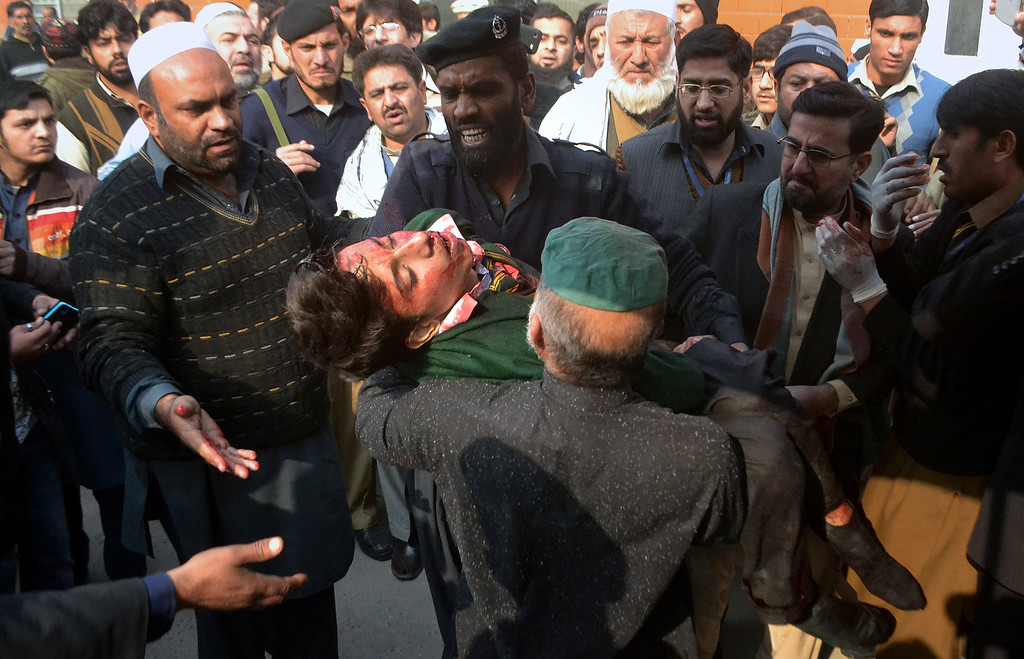 . Hospital security guards carry a student injured in the shootout at a school under attacked by Taliban gunmen in Peshawar, Pakistan,Tuesday, Dec. 16, 2014. Taliban gunmen stormed a military school in the northwestern Pakistani city, killing and wounding dozens, officials said, in the latest militant violence to hit the already troubled region. (AP Photo/Mohammad Sajjad)(AP Photo/Mohammad Sajjad)