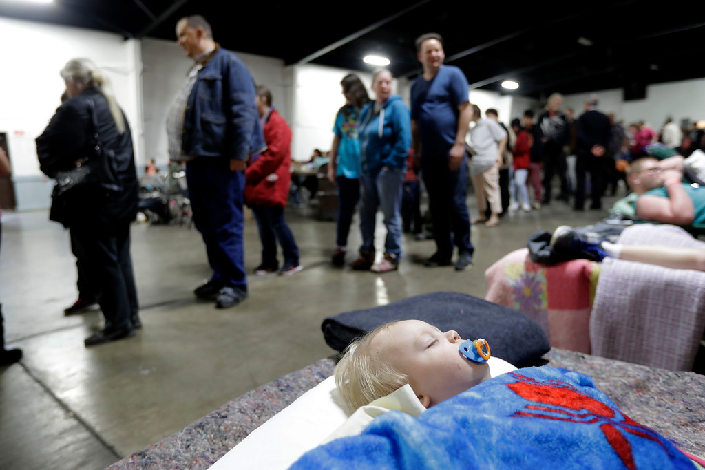 . Jace Lawson, 1, of Oroville, Calif., bottom, sleeps as people behind wait for a meal at a shelter for evacuees from city\'s surrounding the Oroville Dam, Monday, Feb. 13, 2017, in Chico, Calif. The thousands of people who were ordered to leave their homes after a damaged California spillway threatened to unleash a 30-foot wall of water may not be able to return until significant erosion is repaired, authorities said Monday. (AP Photo/Marcio Jose Sanchez)