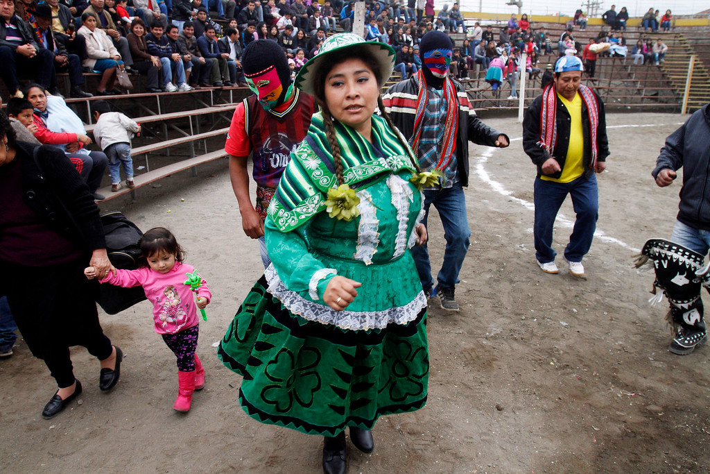 ". Participants of the Takanakuy fighting ritual dance before the start of the event in Lima, Peru. The Andean fight known as Takanakuy are preceding with traditional dancing and music. During the fights, women sing ""huaylia\"" music with lyrics in Quechua that include such lines as \""Child, fear not when rivers of blood flow.\"" (AP Photo/Karel Navarro)"