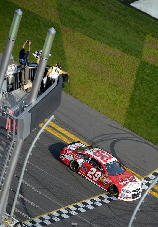 . Driver Kevin Harvick takes the checkered flag as he crosses the finish line to win the first of two 150-mile qualifying races for the NASCAR Daytona 500 auto race at Daytona International Speedway, Thursday, Feb. 21, 2013, in Daytona Beach, Fla. (AP Photo/Phelan M. Ebenhack)
