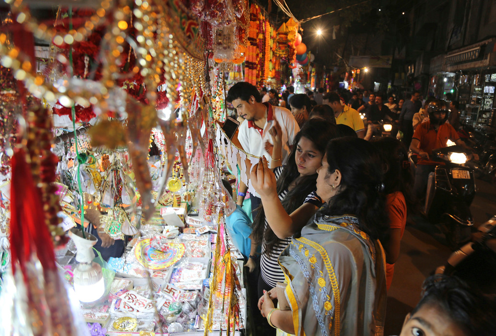 . Indians shop for decorative items on the eve of Diwali, the Hindu festival of lights, in Jammu, India, Wednesday, Oct. 18, 2017. Hindus light up their homes and pray to Lakshmi, the goddess of wealth, during the festival which will be celebrated on Thursday. (AP Photo/Channi Anand)