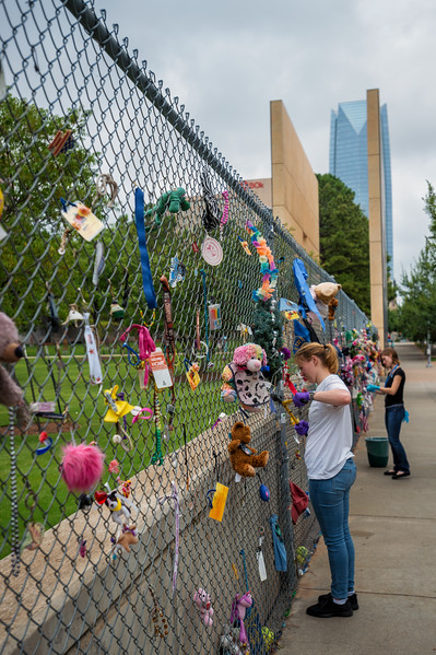 August 7, 2017:  Volunteers clear some mementos from the chain link fence along the Oklahoma City National Memorial, site of the April 19, 1995 bombing of the Alfred P. Murrah Federal Building in Oklahoma City, Oklahoma. Older mementos that have begun to rust are removed regularly and preserved in the museum's archive.