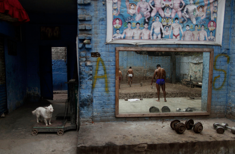 Description of . A dog looks at Pakistani Kushti wrestlers, right, reflected on a mirror, attend their daily training session in Lahore, Pakistan, Tuesday, Feb. 26, 2013. Kushti, an Indo-Pakistani form of wrestling, is several thousand years old and is a national sport in Pakistan. (AP Photo/Muhammed Muheisen)
