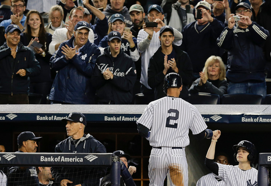 . New York Yankees\' Derek Jeter is greeted by teammates and applauded by fans as he enters the dugout after scoring against the Baltimore Orioles in the first inning a baseball game, Thursday, Sept. 25, 2014, in New York. (AP Photo/Julie Jacobson)