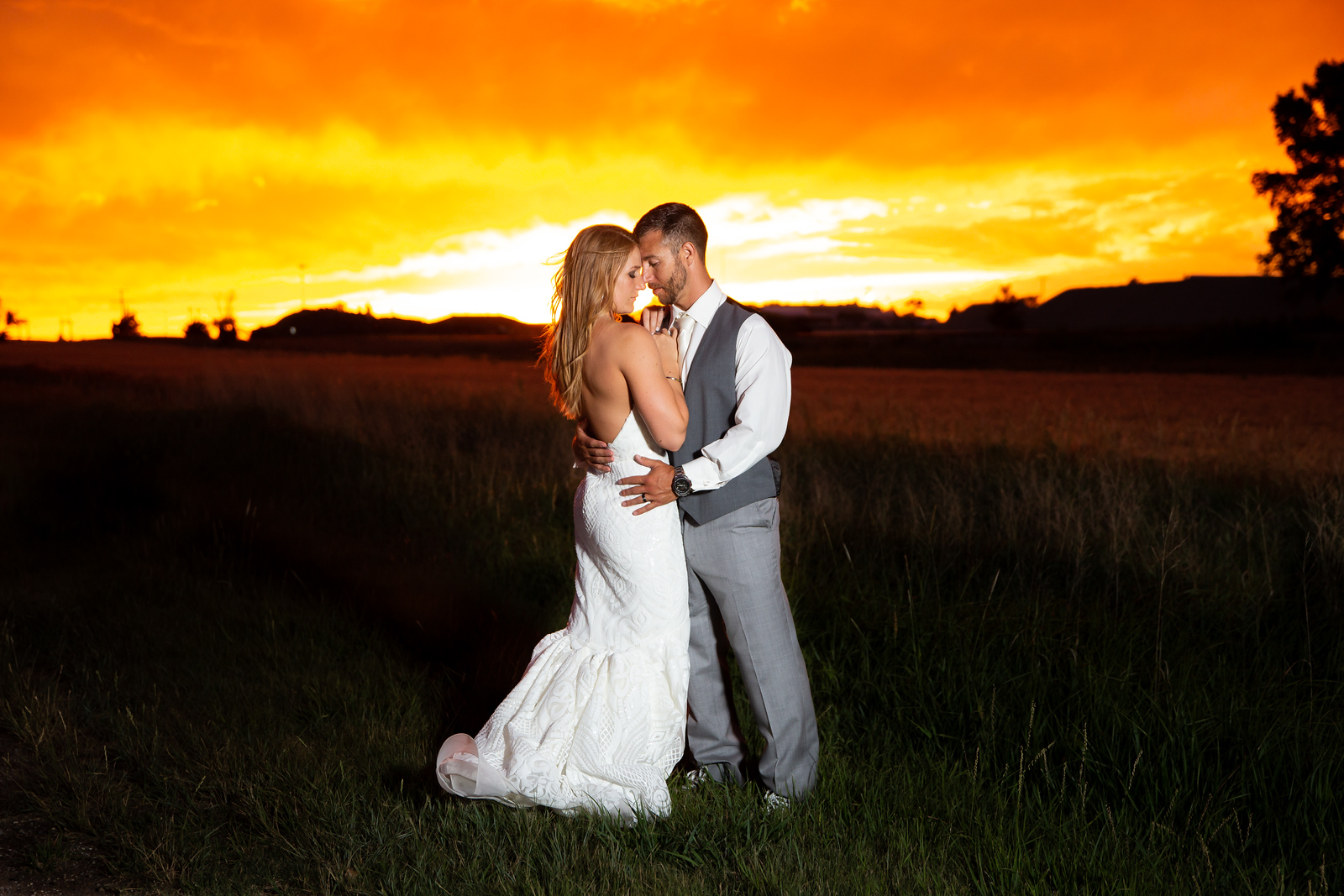 bride and groom share an embrace at sunset