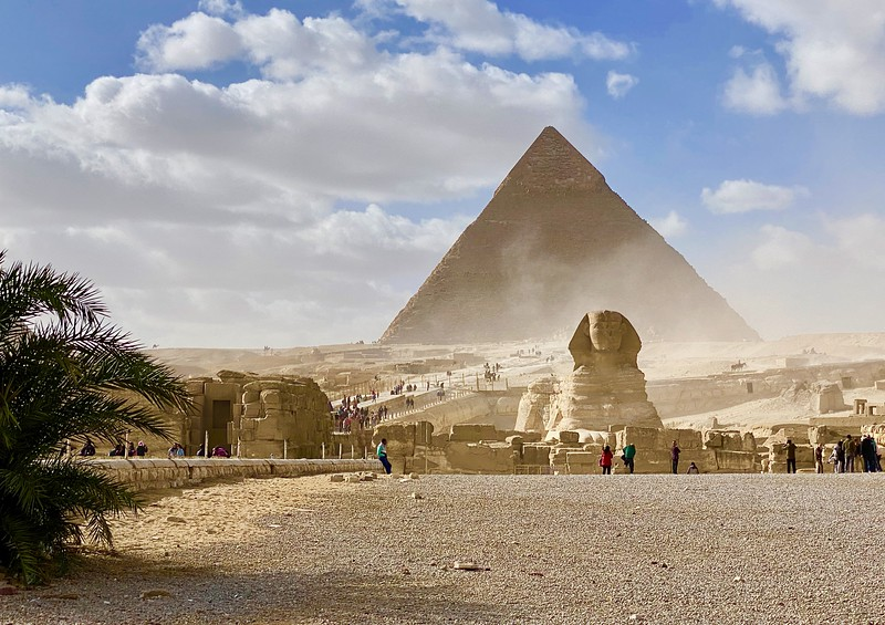 The Sphynx sits in front of a pyramid with dust blowing in the air.