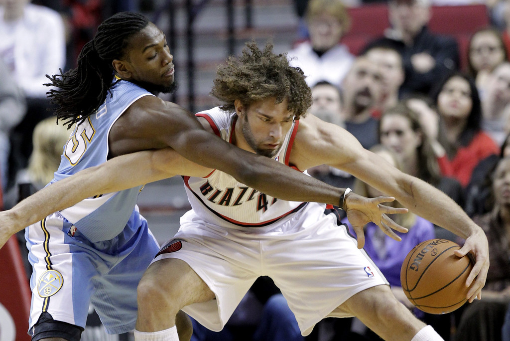 . Denver Nuggets forward Kenneth Faried, left, reaches in on Portland Trail Blazers center Robin Lopez during the first half of an NBA basketball game in Portland, Ore., Saturday, March 1, 2014. (AP Photo/Don Ryan)