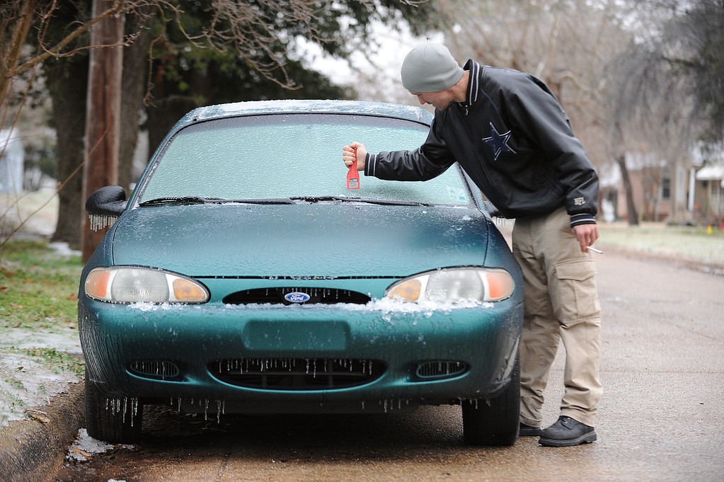 . Chris Harris of Shreveport, La., chips away at the ice that formed on his car Wednesday, Feb. 12, 2014, in Shreveport, La., after a winter blast hit the area causing power outages and making for hazardous driving conditions. (AP Photo/The Shreveport Times, Douglas Collier)