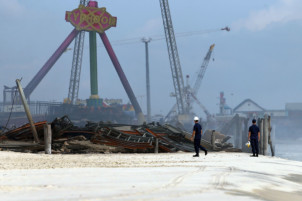 . Two people walk near the destroyed remains of businesses along an iconic Jersey shore boardwalk on September 13, 2013 in Seaside Heights, New Jersey.  (Photo by Spencer Platt/Getty Images)
